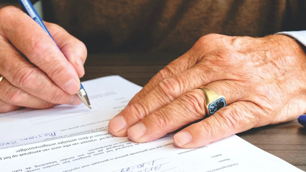 This article is about who pays closing costs in Broward County Florida. The image is of an older man signing a contract.